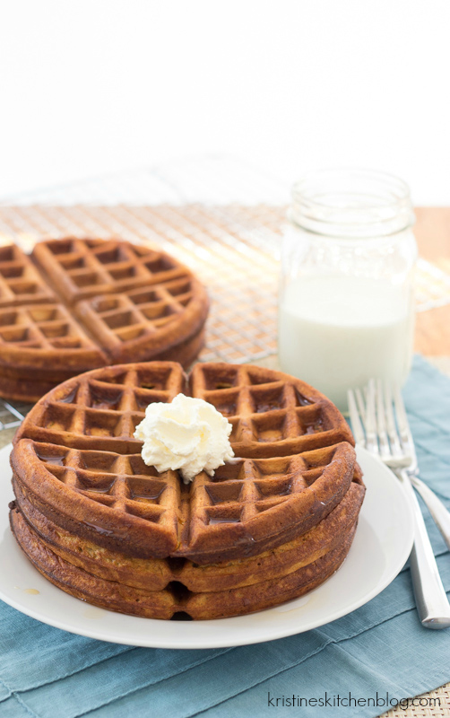 gingerbread waffles stack on a plate and topped with butter