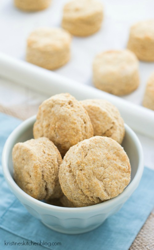 Homemade whole wheat biscuits in a bowl and on a baking sheet.
