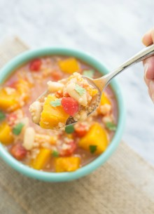 top view of bowl of butternut squash, white beans, quinoa, tomatoes and broth with a spoon