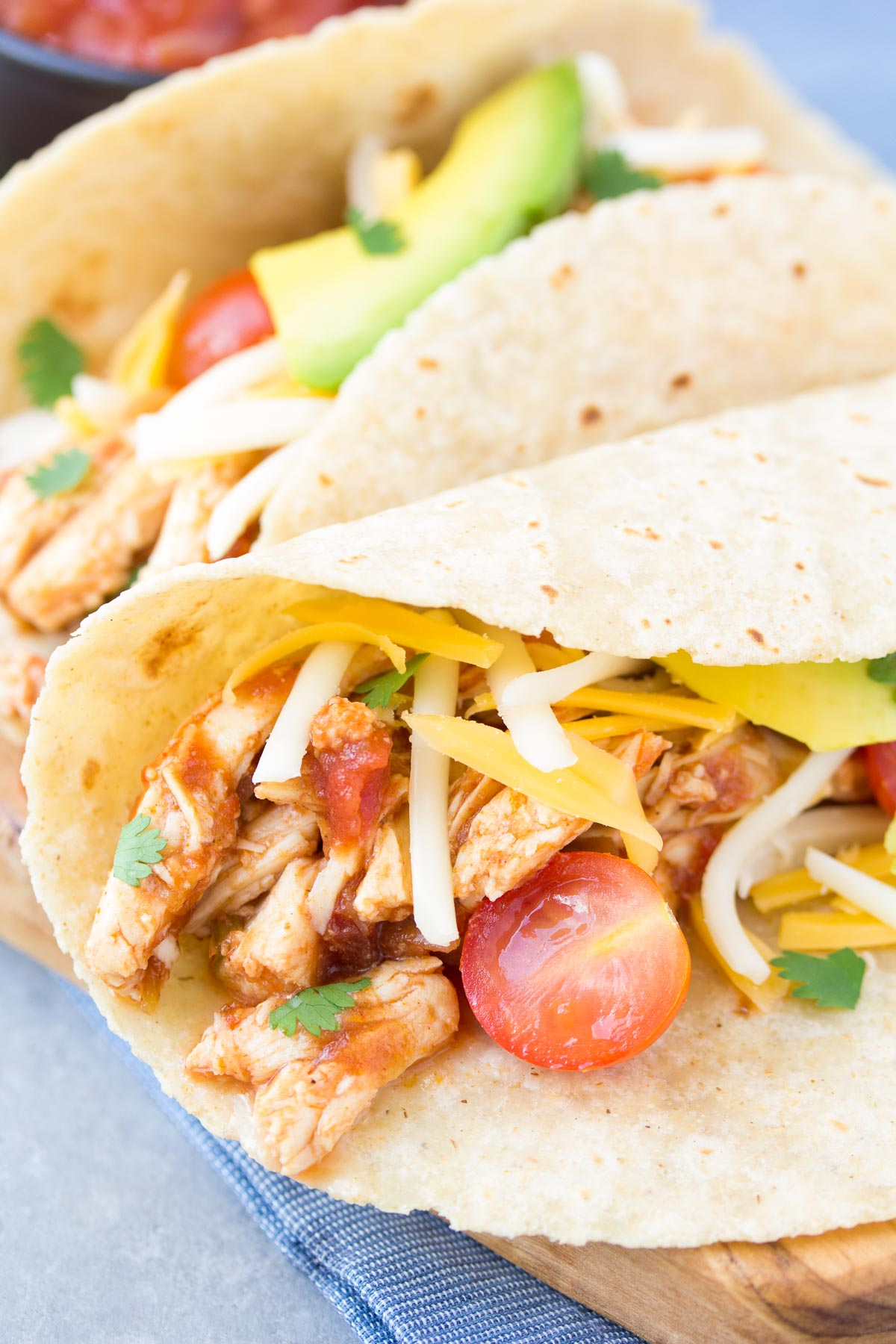 Shredded chicken tacos with salsa, cheese and avocado.