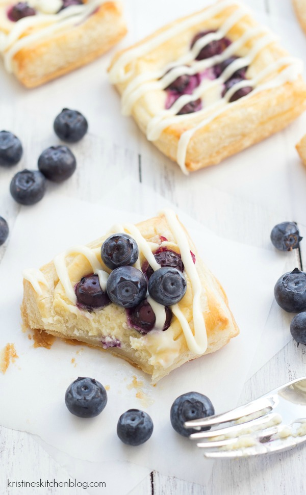 glazed cream cheese danish topped with blueberries missing a bite with a fork