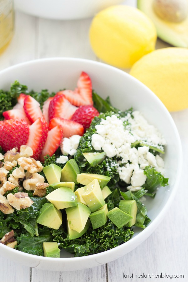 strawberry kale salad in a bowl with avocado, walnuts and cheese
