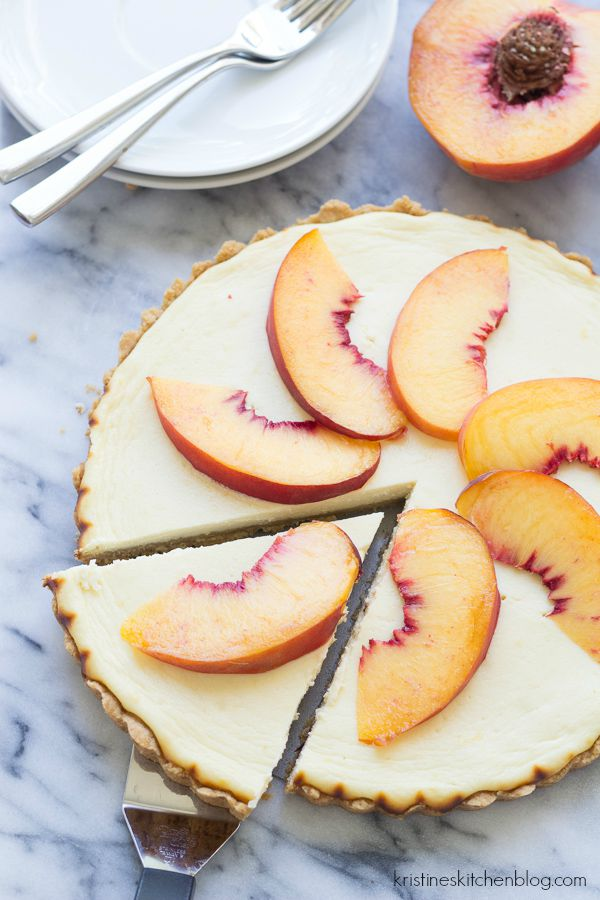 cheesecake topped with fresh peaches with one slice being removed
