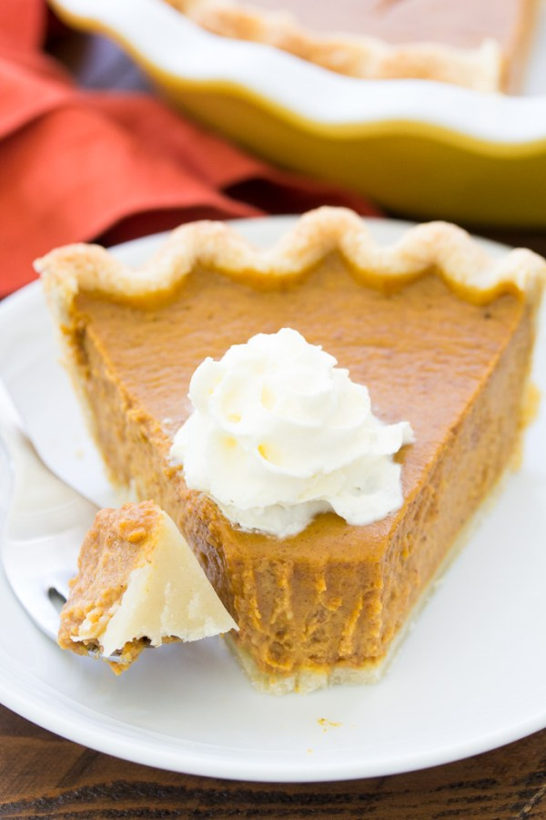 A slice of pumpkin pie with a bite on a fork.