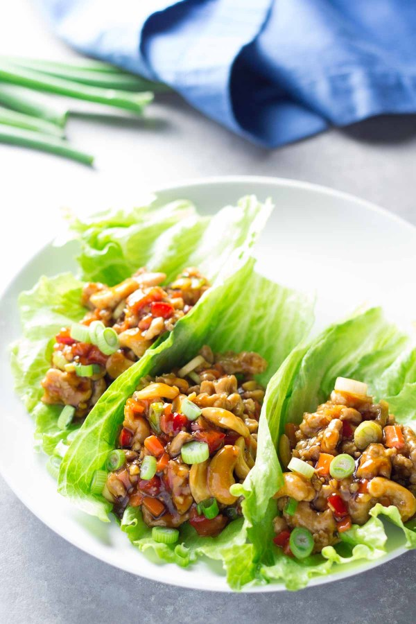 Chicken lettuce wraps with cashews on a white plate.