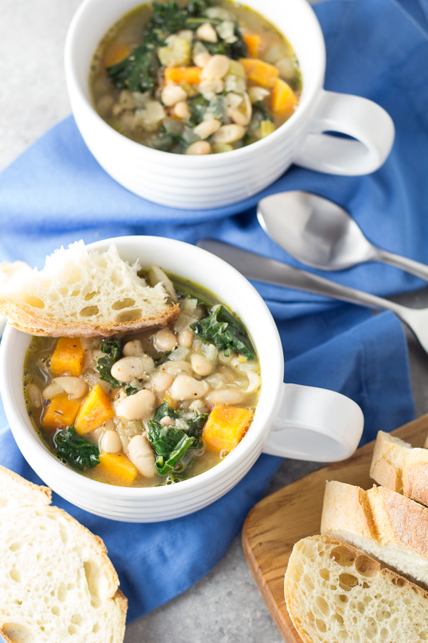 ready to eat white bean and kale soup with slice or bread and spoon