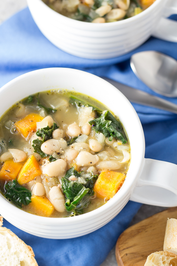 cup of soup with white beans, kale and butternut squash
