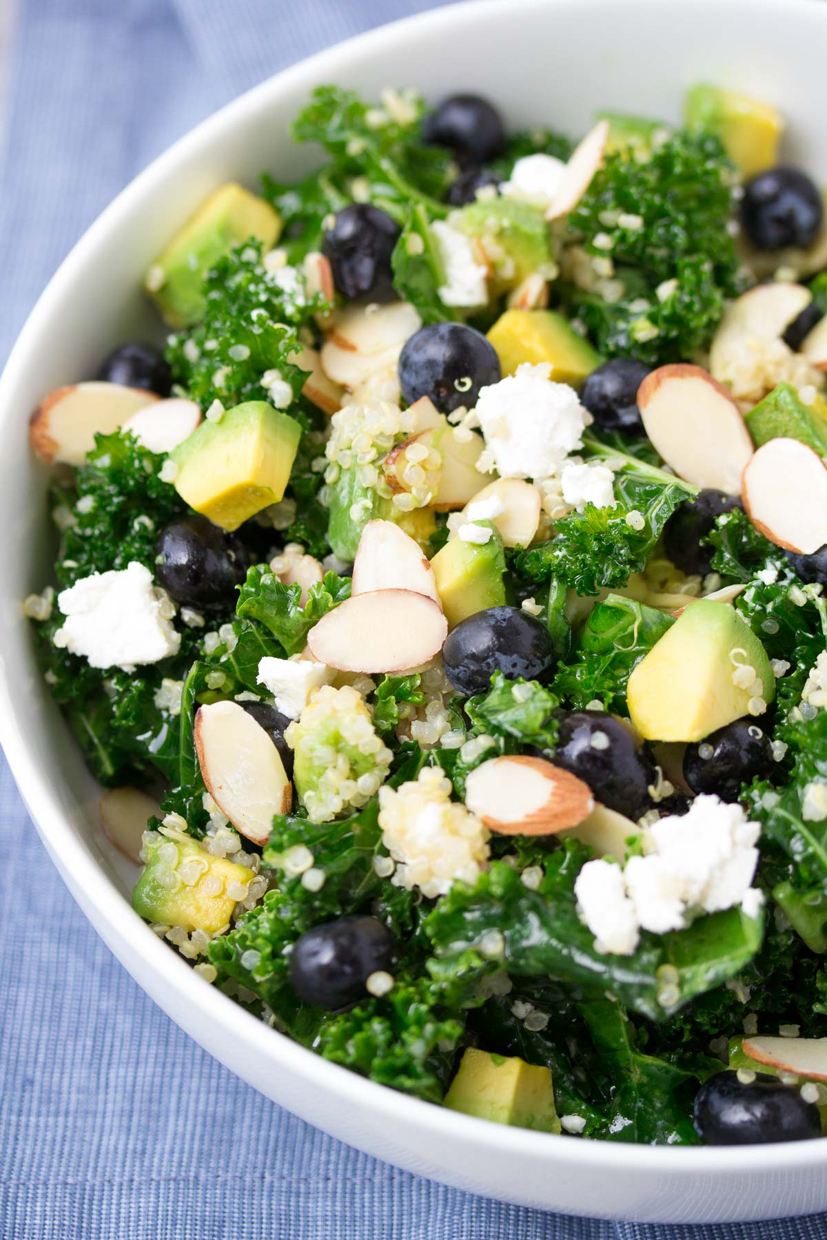 tossed kale quinoa salad with avocado, blueberries, goat cheese and almonds
