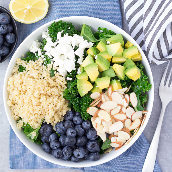 kale salad with avocado, blueberries, quinoa, feta and sliced almonds