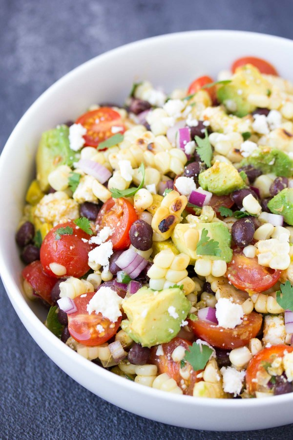 This Summer Grilled Corn Salad is full of avocado, black beans, and Cotija cheese, along with a chili-lime Mexican dressing. A yummy side dish for summer!