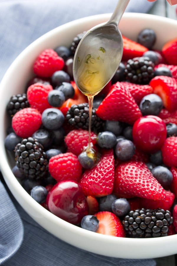 Drizzling honey lime dressing onto fresh berry fruit salad.
