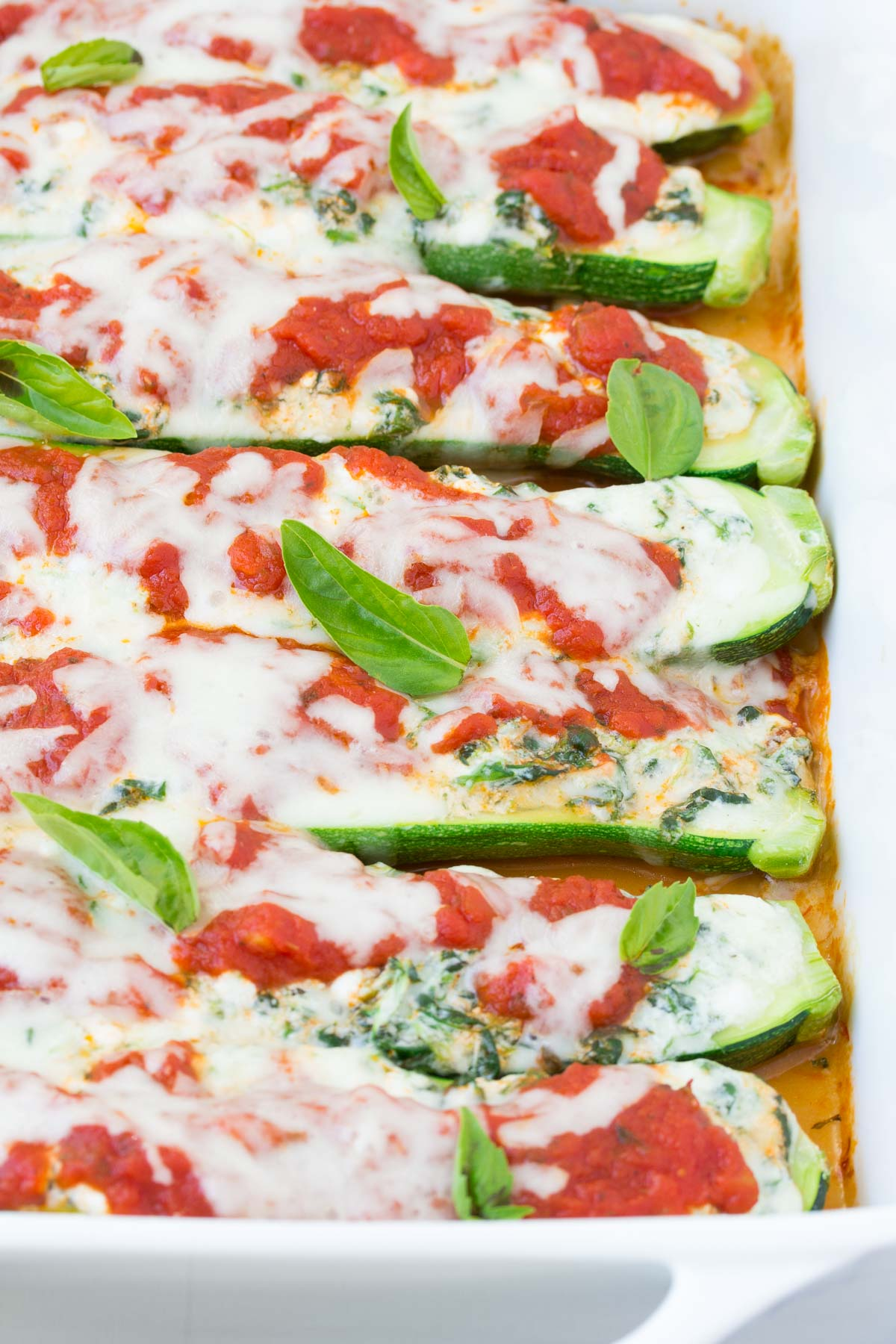 closeup view of baked stuffed zucchini in white baking dish