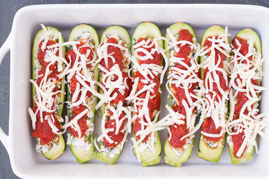 step of stuffed zucchini before baking topped with sauce and cheese