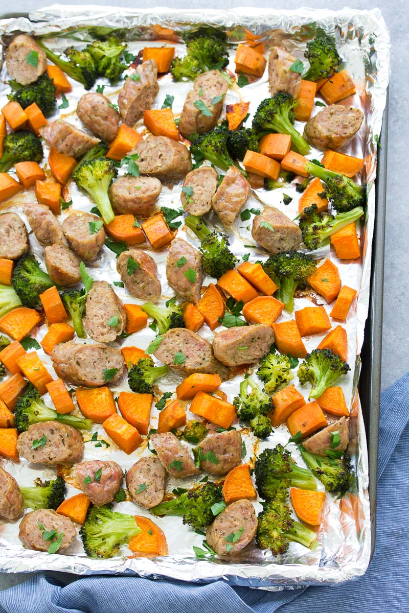 Cooked sausage, broccoli and sweet potatoes on a baking sheet.