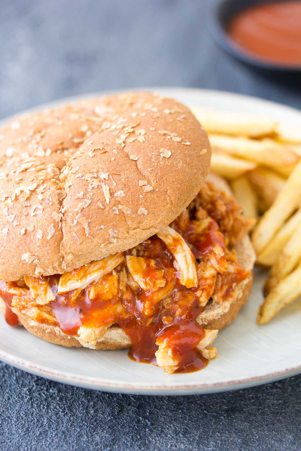 bbq chicken served on a burger bun with french fries