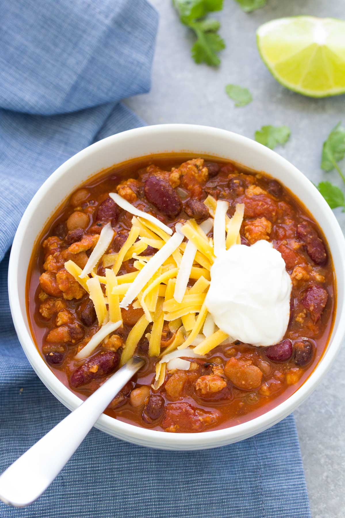 turkey chili in a white bowl topped with cheese and sour cream