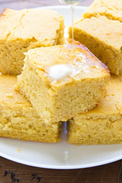 Sweet honey cornbread on a plate, with melted butter and honey drizzle.