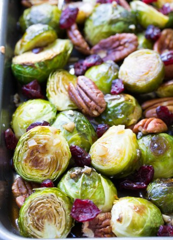 Roasted Brussels Sprouts with maple balsamic glaze, pecans and garlic on a baking sheet.