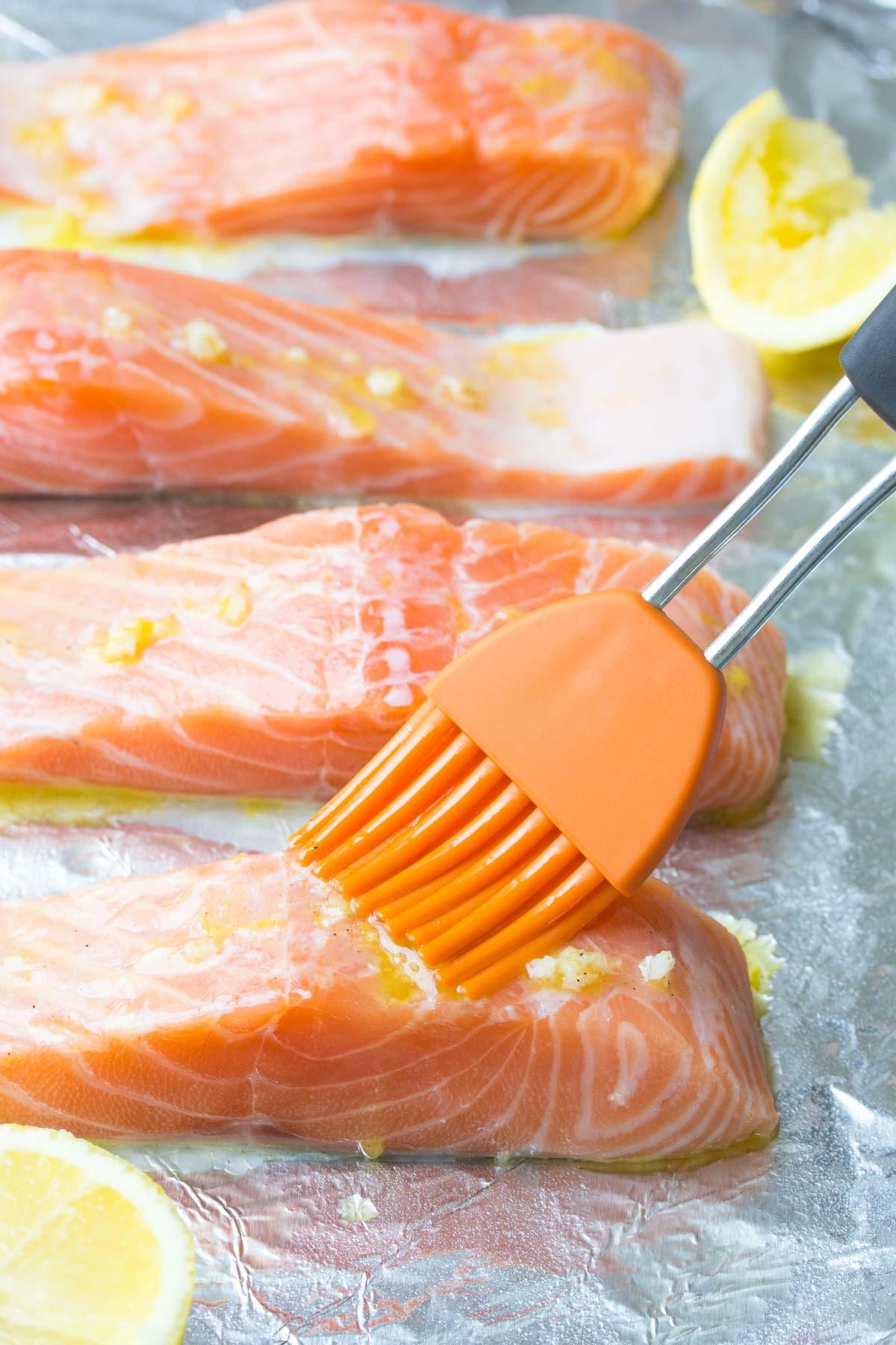 salmon filets brushed with lemon garlic sauce on a sheet pan