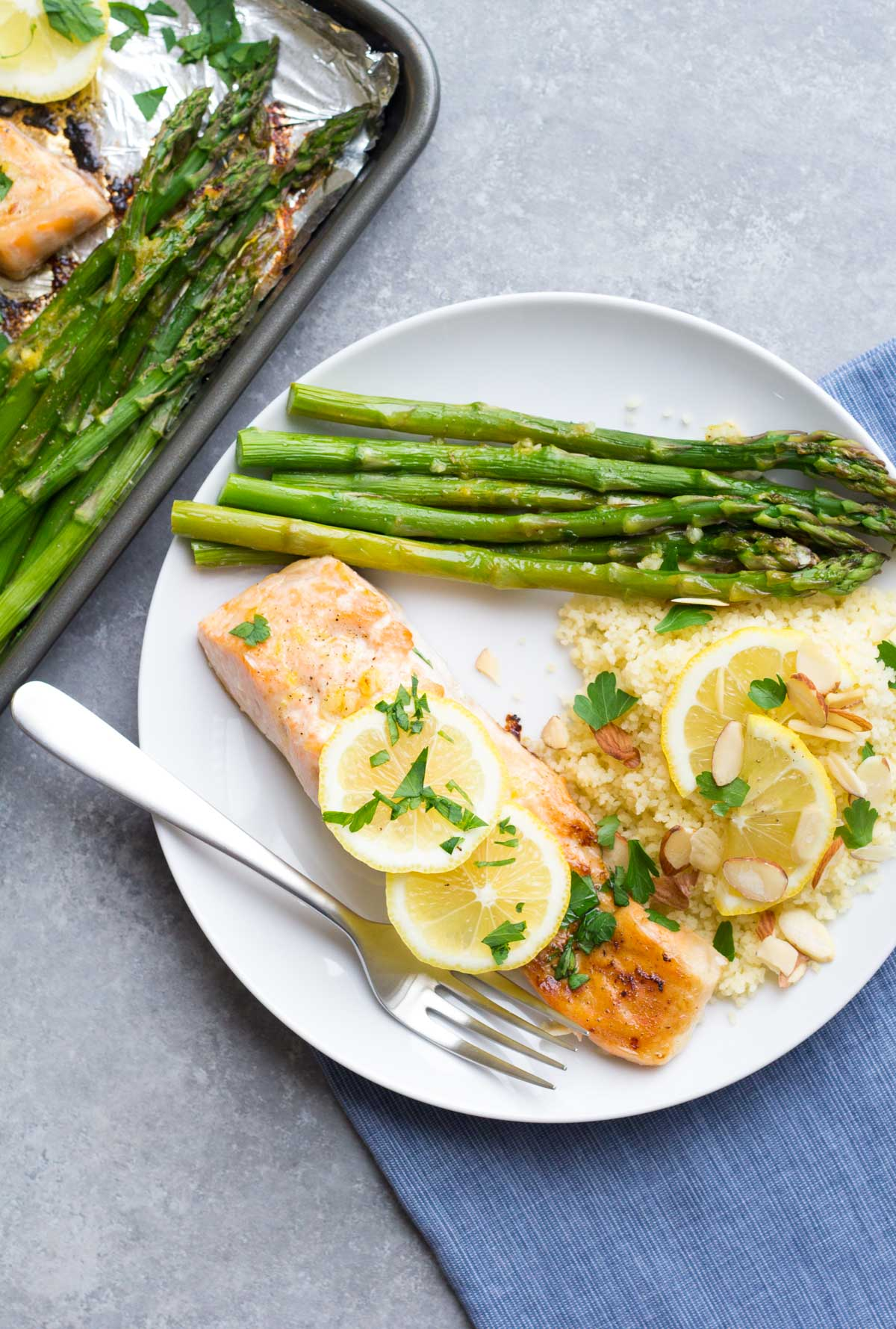 overhead view of baked lemon garlic salmon on plate with sides of asparagus and couscous