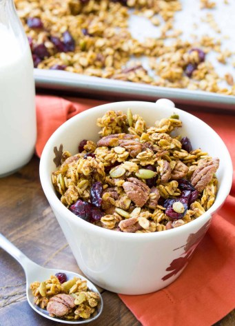 pumpkin spice granola in a cup with a spoonful and granola and milk in background