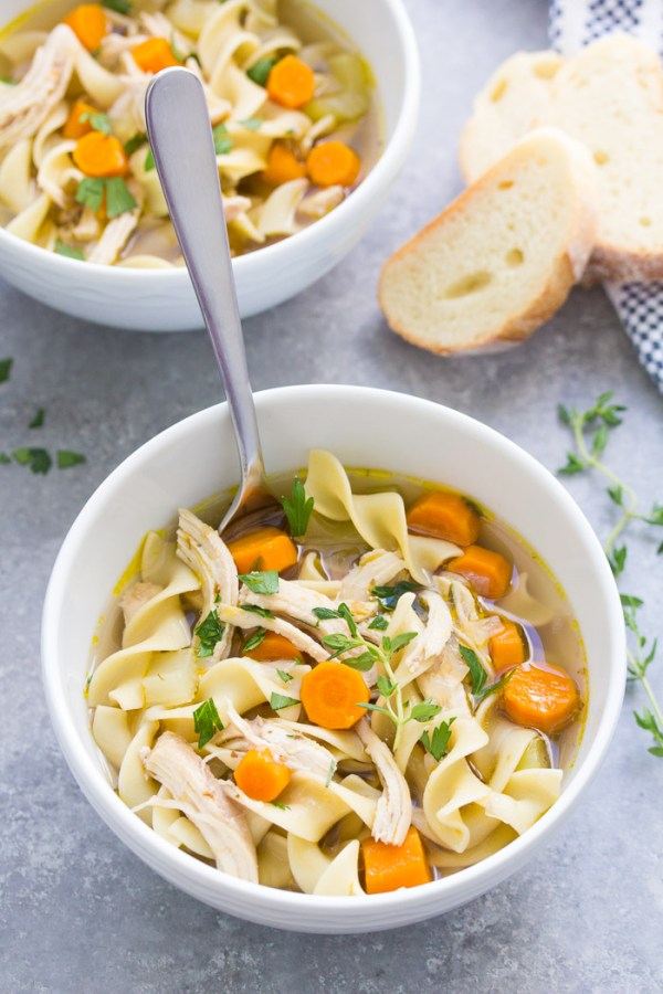Pressure cooker chicken noodle soup in a white bowl with a spoon.