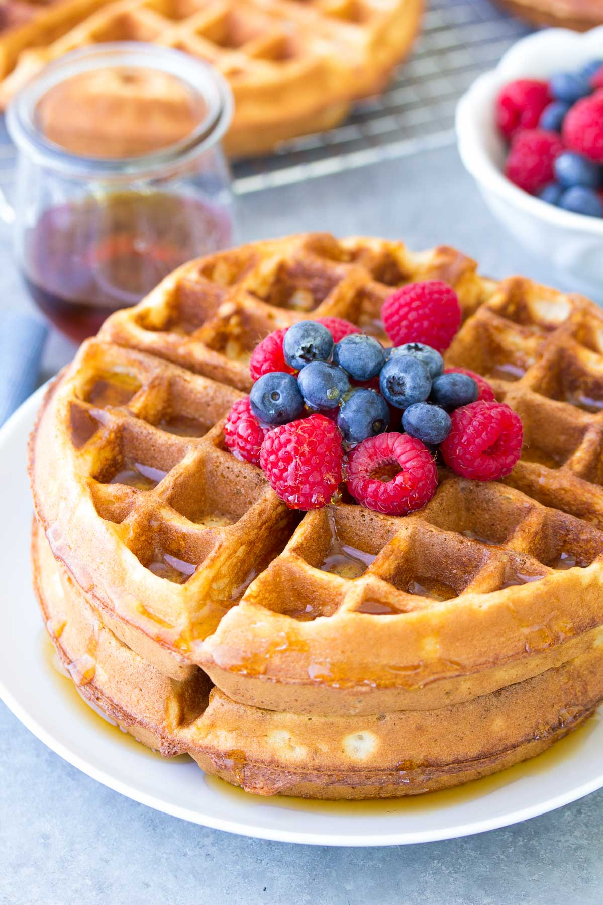 waffles on a plate with fresh berries and syrup on top