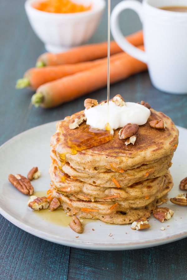 Healthy Carrot Cake Pancakes with maple yogurt are great for breakfast or kids' lunch boxes! Top them with maple Greek yogurt and toasted nuts or serve with maple syrup. These easy carrot cake pancakes are refined sugar free and freeze well for meal prep breakfasts.