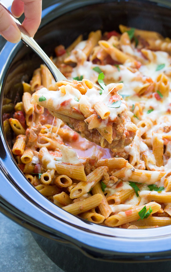 This Slow Cooker Baked Ziti is made with ground turkey and whole wheat pasta. The pasta cooks right in your crock pot so it soaks up the delicious flavor of the sauce. This healthier slow cooker pasta recipe is a simple comfort food dinner for your family!