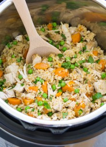 Chicken and rice with vegetables, in an Instant Pot with a serving spoon.