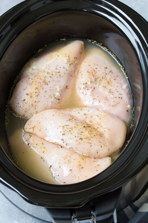 Chicken in a slow cooker to make crockpot shredded chicken.