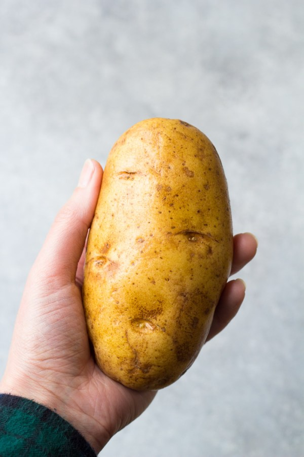 Large Russet potato in hand. Easy Instant Pot Baked Potatoes Recipe.