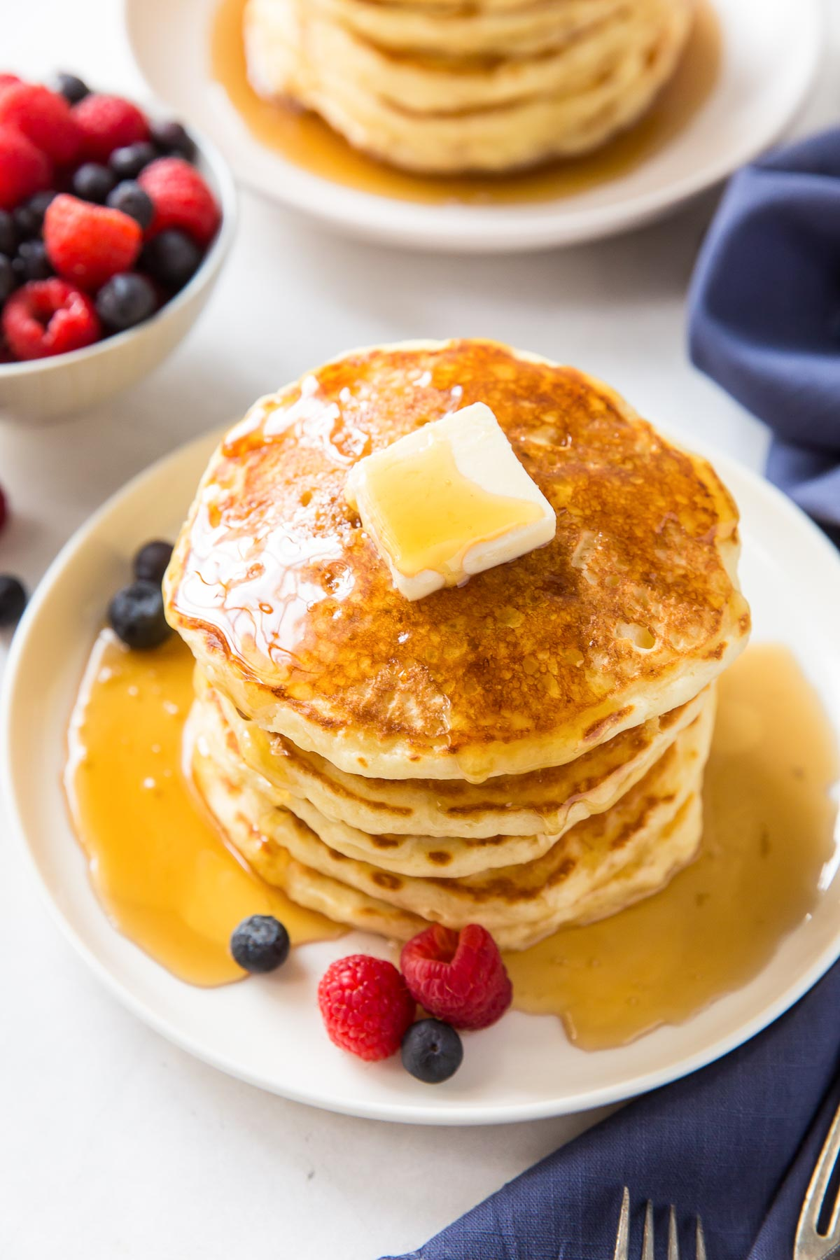 stack of pancakes served with butter, syrup and berries