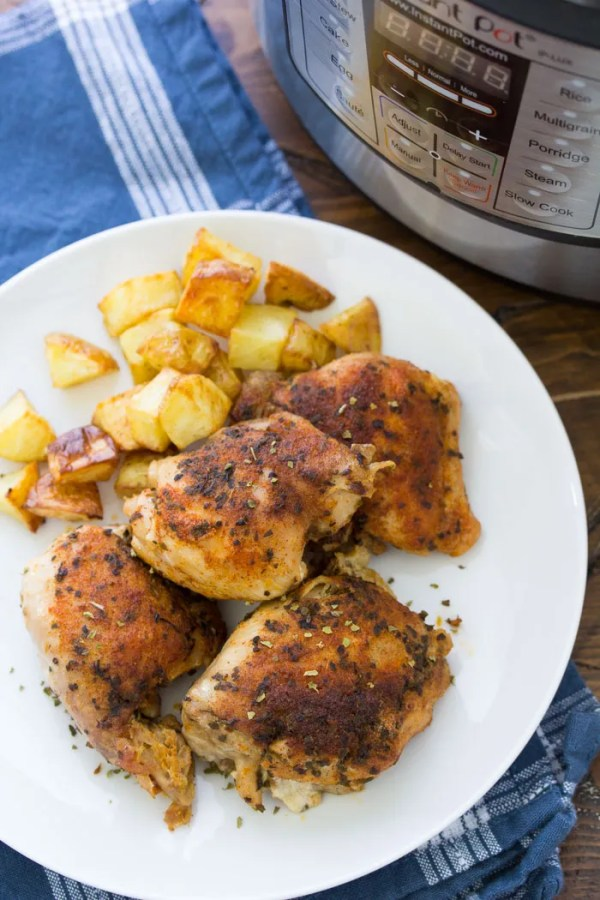 Instant Pot Chicken Thighs on a plate with roasted potatoes.