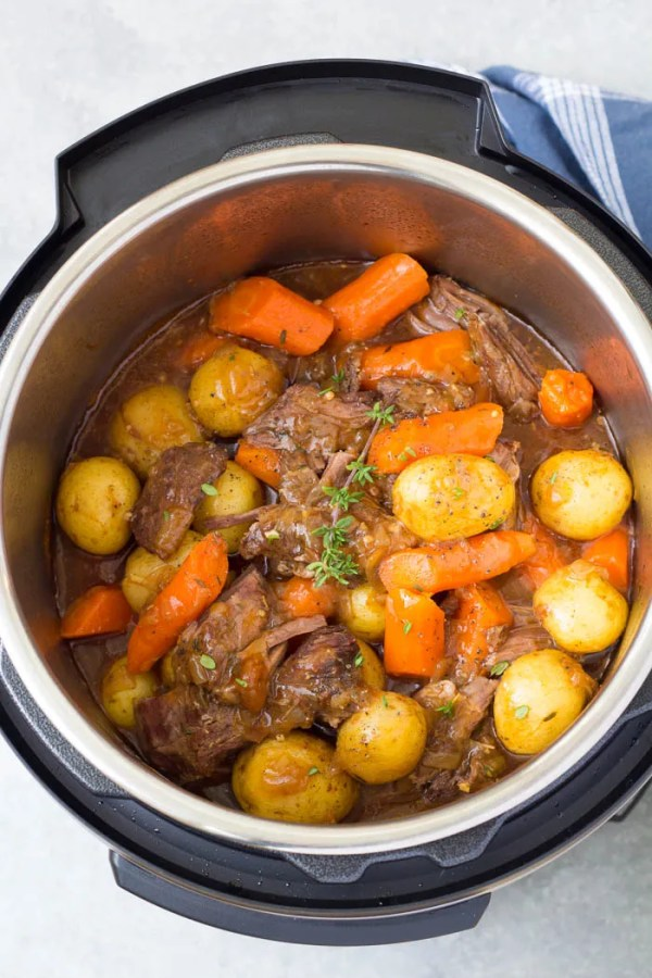 Instant Pot Pot Roast with potatoes and carrots in the pressure cooker after cooking. One of our favorite pressure cooker recipes!