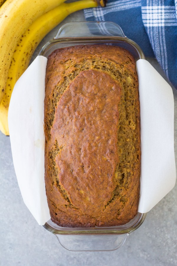 Baked loaf of healthy banana bread in a loaf pan with parchment paper overhang.