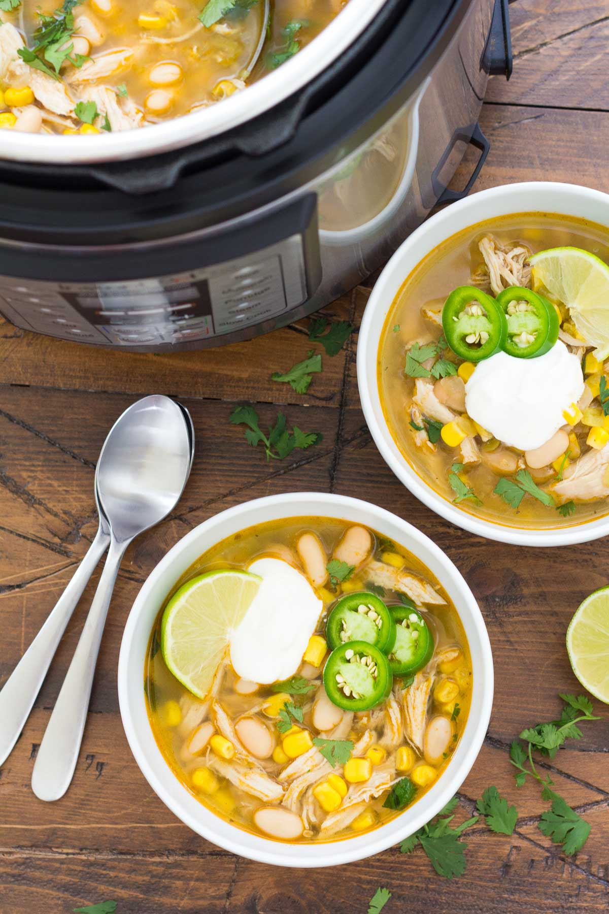 two bowls of instant pot white chicken chili next to an instant pot