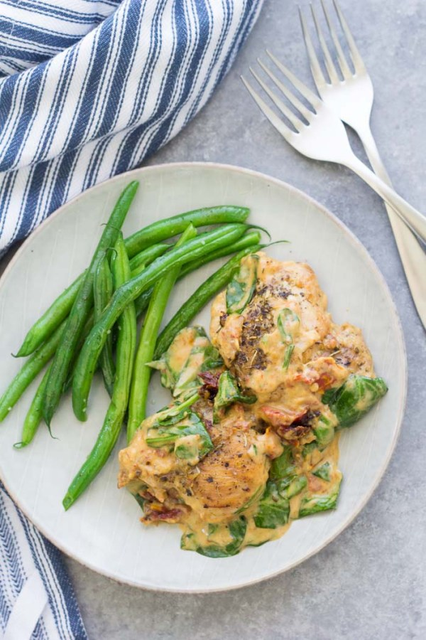Creamy Tuscan Slow Cooker Chicken Thighs with spinach, sun dried tomatoes and green beans.