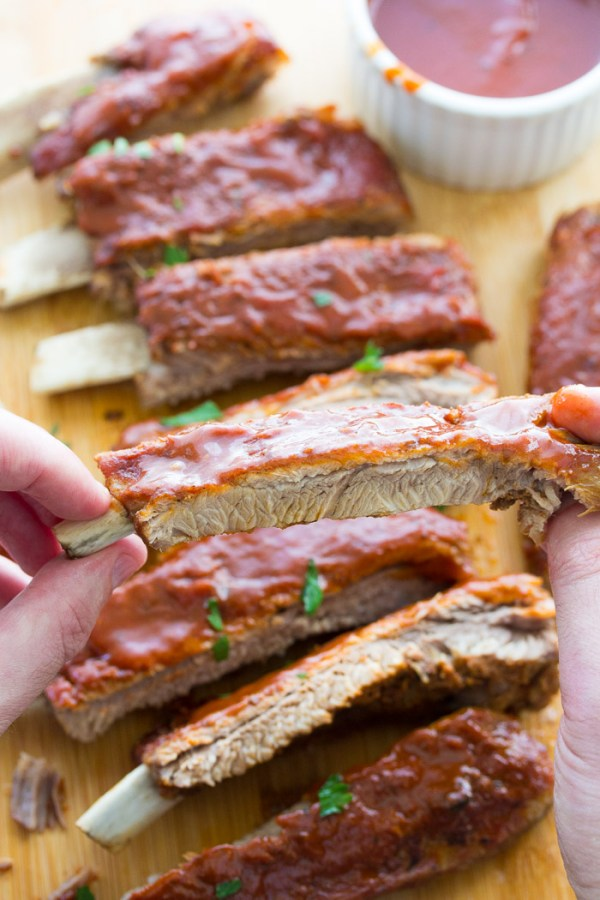 Fingers holding Instant Pot ribs with bbq sauce.