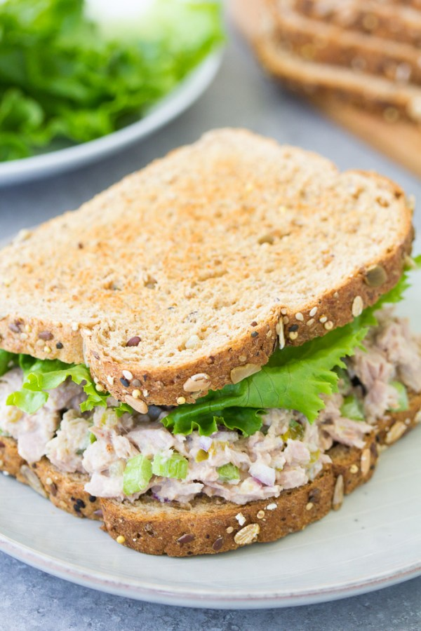 Tuna salad sandwich on toasted bread with lettuce.