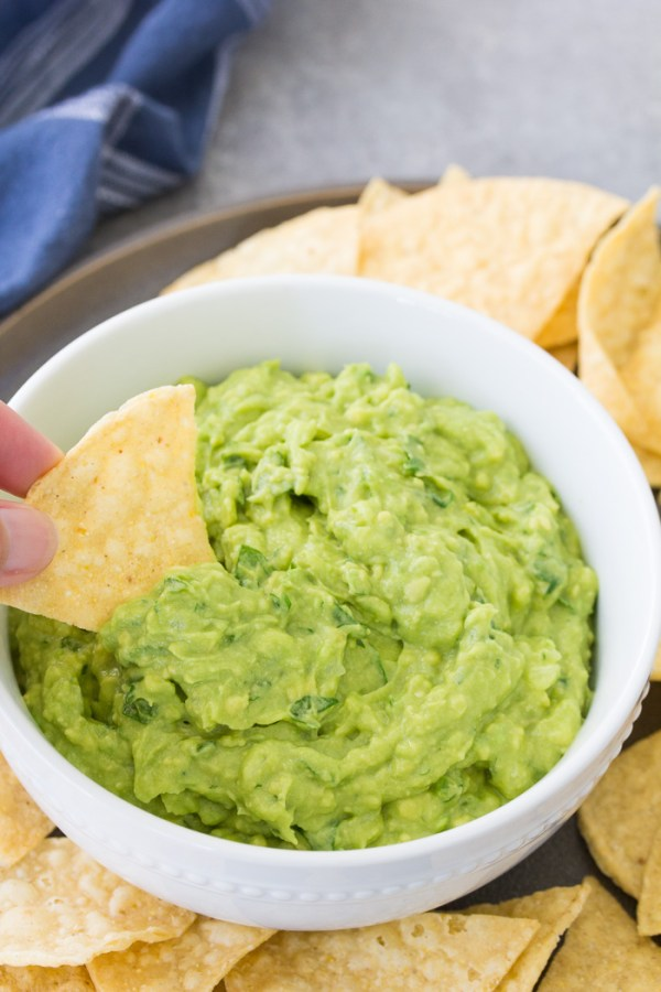 Bowl of guacamole with a chip being dipped into it.