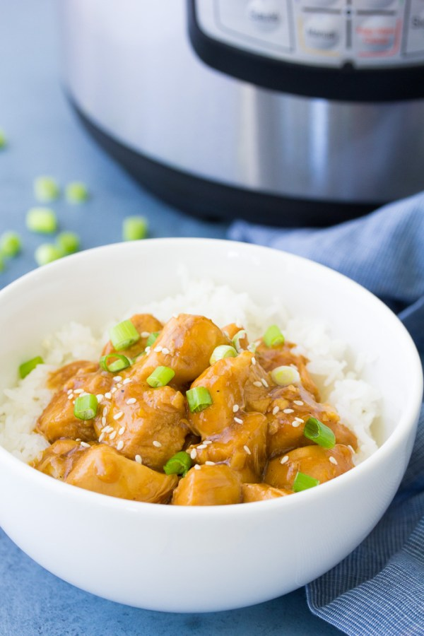 Side view of instant pot orange chicken with rice, with an instant pot in the background.