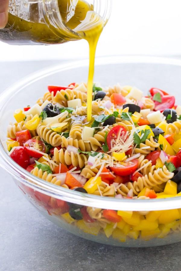 Pouring homemade Italian dressing onto a pasta salad.