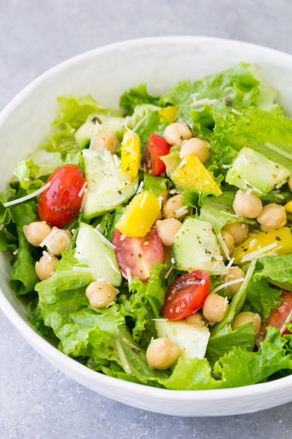 Green salad with cucumber, chickpeas and tomatoes, drizzled with Italian dressing.