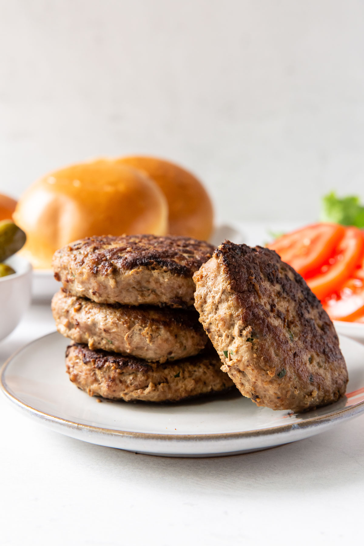 three turkey burgers stacked on a plate with a fourth burger leaning against the stack