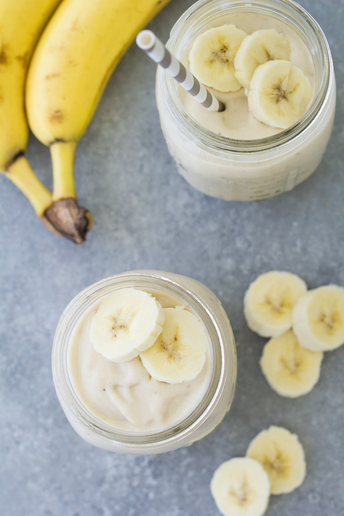 Top down view of two banana smoothies with sliced bananas around.