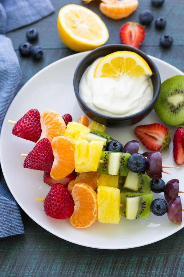 Rainbow fruit skewers stacked on a plate, next to a bowl with Greek yogurt dip.