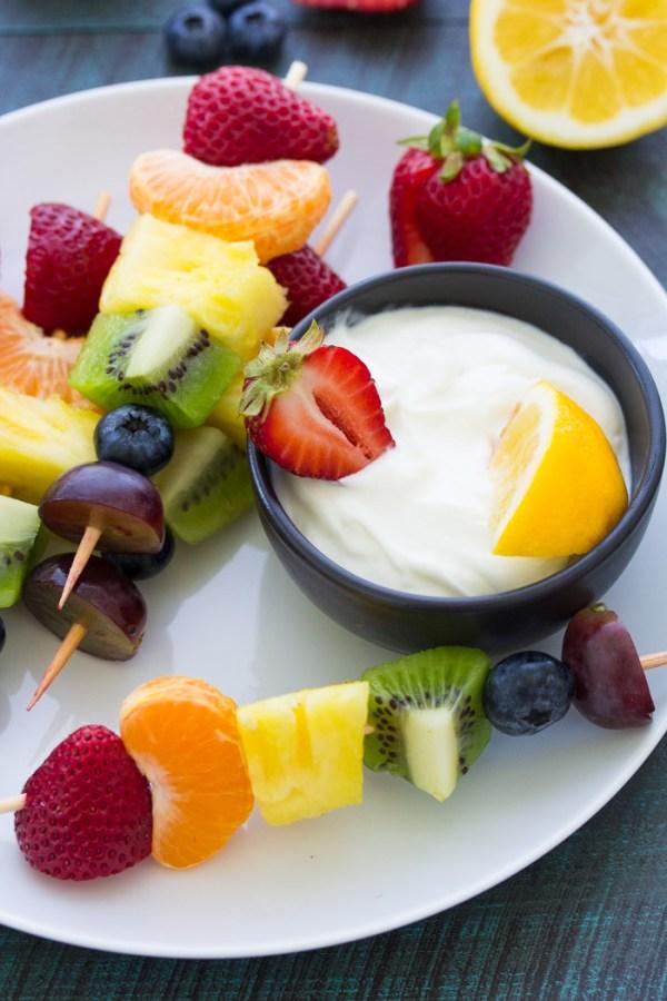 Fruit kabobs served with a bowl of creamy lemon greek yogurt dip.