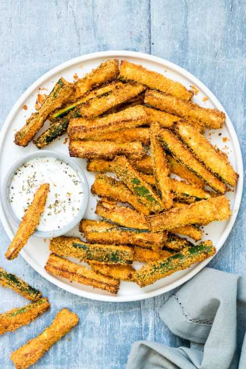 Air Fryer Zucchini Fries on a plate with dipping sauce.