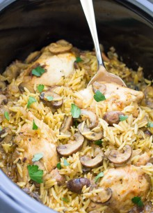Chicken, mushrooms and orzo in a slow cooker with a serving spoon.